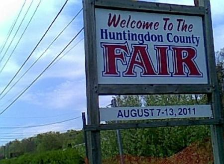 Huntingdon County Fair sign with green trees and blue skies with white clouds