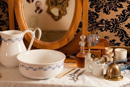 white bowl, pitcher, gold bell and an antique mirror in a shop