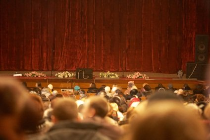 people at a theatre in Pennsylvania with a rust colored stage curtain