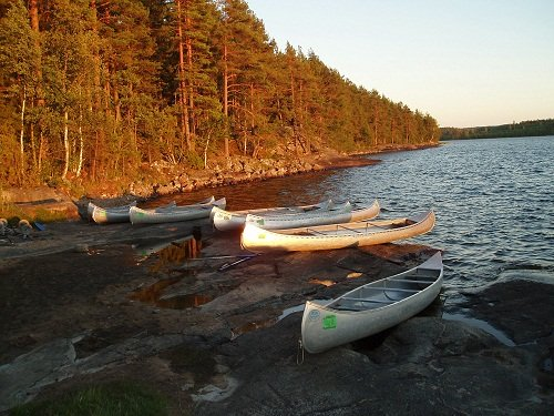 five canoes by the water at camp