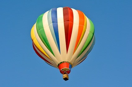 Pocono Balloon Festival green, white, blue, yellow, orange and red hot air balloon in the blue sky