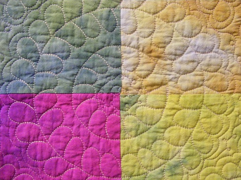 blue, tan and purple colored quilt
