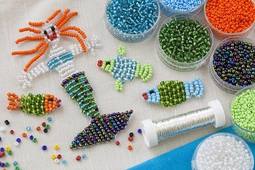 table with blue, green, orange beads in bowls with three fish and a mermaid made from beads