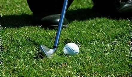 golfing with a club and white ball in the grass