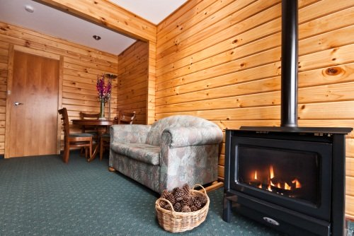 lodge indoors with a fireplace, chair and table with two chairs