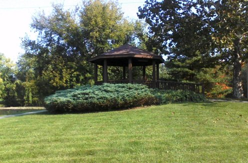 park in PA with green trees, green grass and a brown gazebo overlooking the water