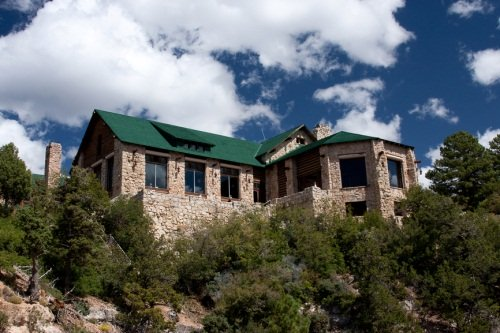 outside view of a lodge surrounded by trees with a dark blue sky and white clouds