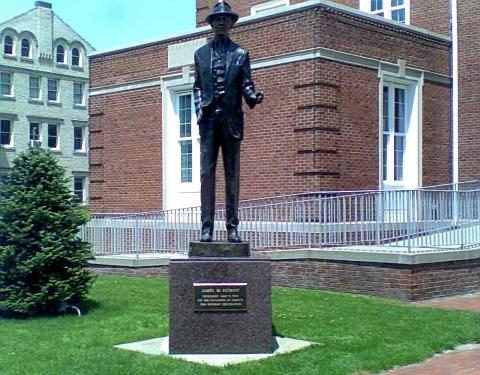 museums in Pennsylvania bronze Jimmy Stewart statue in front of a red brick building with white windows on green grass beside a green bush in Indiana PA