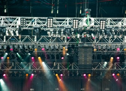 purple, yellow and white spotlights at the outdoor stage before a concert