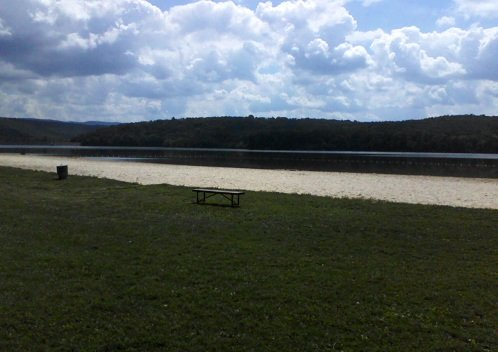 lake in Pennsylvania in September with grass, a bench, sand beach, water, green mountains and white clouds in the blue sky