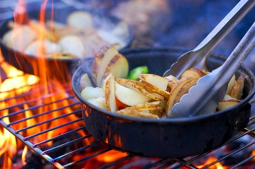 cooking sliced potatoes on the grill at a campsite