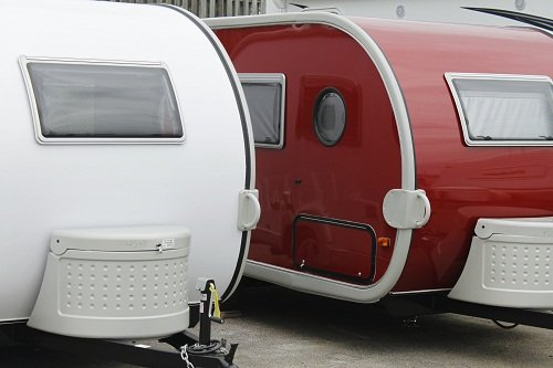 one white and one red travel railer rv