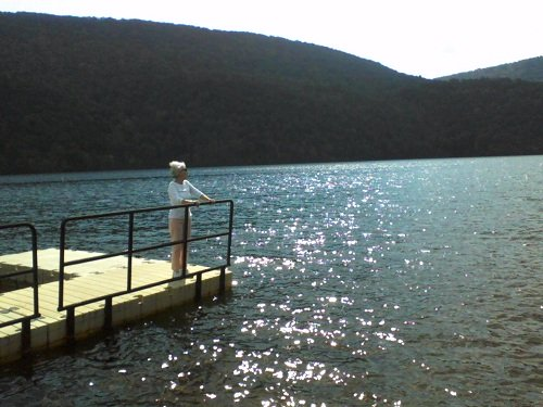 standing on a dock looking out over the brilliant blue water sparkling like diamonds in the sun with mountains behind