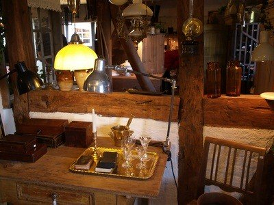 PA antique vintage shop with lamps, glass jars, wooden boxes, a gray tray with long stemmed glasses
