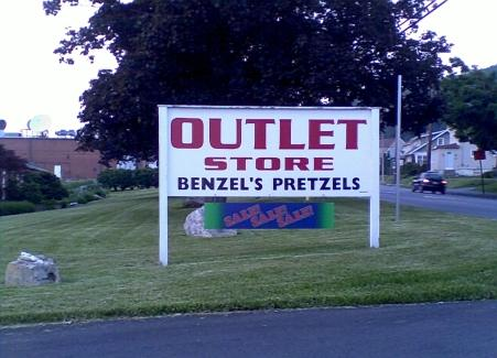 Benzels Pretzels outlet store maroon and white sign on green grass in Altoona PA