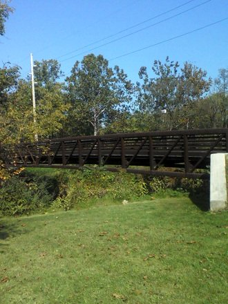 walking bridge over the river with grass and trees in Pennsylvania