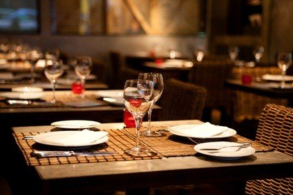 restaurant tables with placemats, plates, silverware and long stemmed glasses