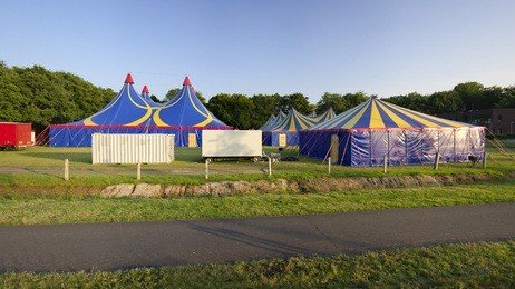 three tents, yellow and blue, at a PA fairgrounds with green grass and green mountains