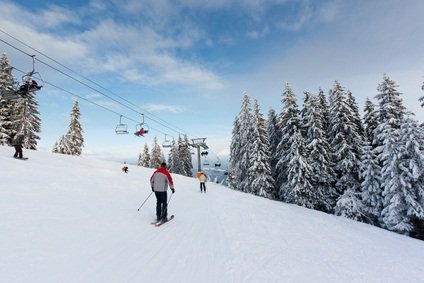 PA skiing resort with snow covered slope and pine trees