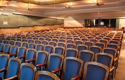 empty rows of blue seats in a theatre