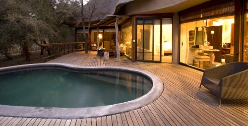 swimming pool outside the deck of a lodge at night with lights on