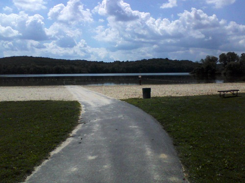 walkway to the sand beach and lake with mountains behind and blue sky and clouds overhead
