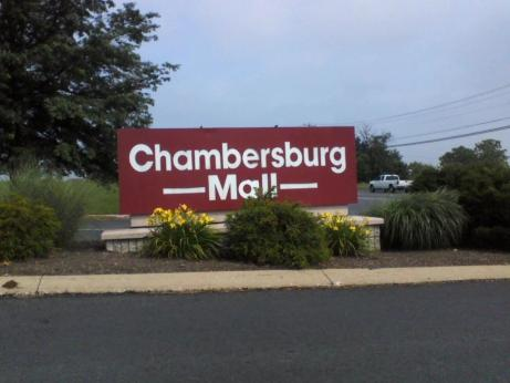 shopping in PA maroon and white Chambersburg Mall sign surrounded by green trees and green bushes in Chambersburg PA, Franklin County PA