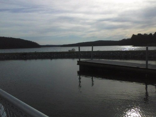 state park in Pennsylvania with a dock, sun sparkling off the water and mountains as a backdrop