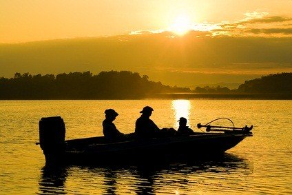 motor boat on a lake as the sun is rising in a gold sky casting a yellow glow on the rippling water with mountain backdrop