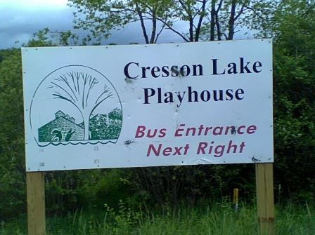 Cresson Lake Playhouse in Loretto PA Cambria County PA blue, green, white and red sign surrounded by green trees and green grass