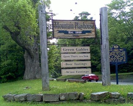 Jennerstown PA Mountain Playhouse and Green Gables restaurant sign surrounded by green trees, green grass and a blue grist mill sign