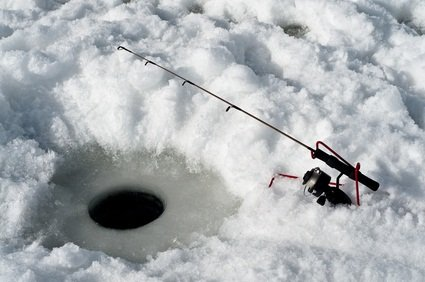round hole in the lake with snow surrounding and a fishing rod